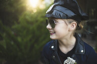 Close-up of smiling girl in police costume wearing sunglasses while standing against plants at yard during Halloween - CAVF62735