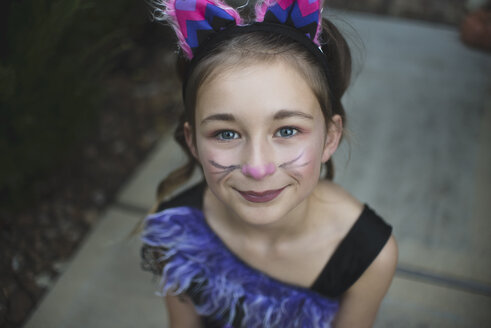 High angle portrait of girl with face paint wearing Halloween costume while sitting in yard during sunset - CAVF62741