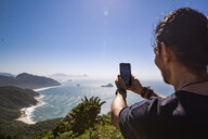Tourist photographing sea with smart phone against sky during sunny day - CAVF62780