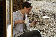 Man holding coffee cup using smart phone while sitting in forest during sunny day - CAVF62786