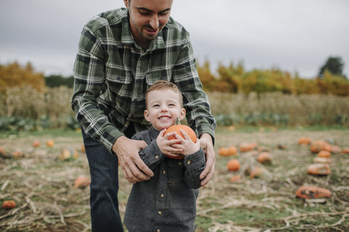 Father helping cute smiling son in holding pumpkin on field during autumn - CAVF62816