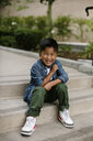 Portrait of cute happy boy sitting on steps at Balboa Park - CAVF62837