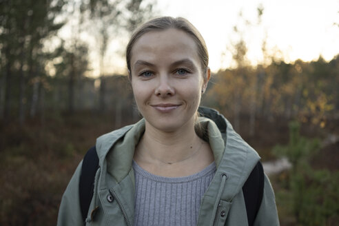 Portrait of smiling woman standing against trees in forest during sunset - CAVF62843