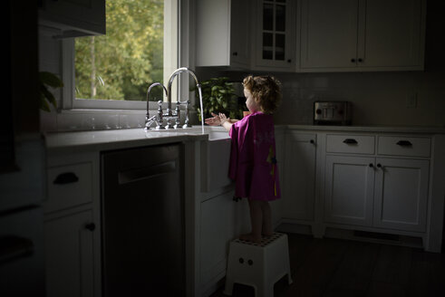 Side view of girl wearing pink cape washing hands in kitchen sink while standing on stool at home - CAVF62870