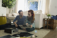 Couple with headphones listening vinyl records living room - HEROF27633
