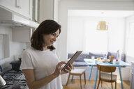 Brunette woman using digital tablet in kitchen - HEROF27654