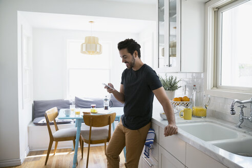 Casual man texting with cell phone in kitchen - HEROF27657