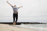 Exuberant woman jumping for joy on beach - HEROF27666