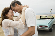 Couple smiling and hugging near convertible at beach - HEROF27675