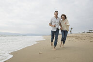 Energetic couple running on beach - HEROF27681