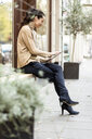 Mature woman sitting in front of her fashion store, using tablet - PESF01518