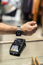 Customer paying contactless with his smartwatch - PESF01527