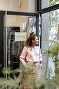Young woman standing in open shop door, smiling - PESF01533