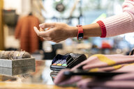 Customer paying contactless with her smartwatch - PESF01539