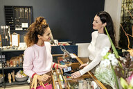 Young customer paying contactless in a fashion store - PESF01542
