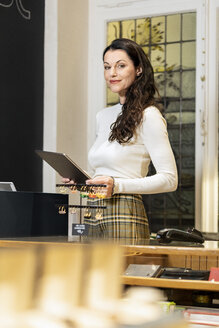 Mature woman working in fashion store, using digital tablet - PESF01545