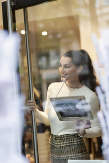 Mature woman standing in shop , smiling, with open sign hanging in window - PESF01554