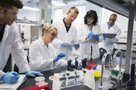 Science professor guiding students in scientific experiment laboratory - HEROF27725