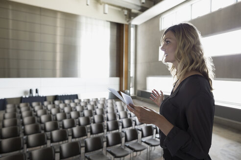 Woman reviewing notes on stage in empty auditorium - HEROF27773