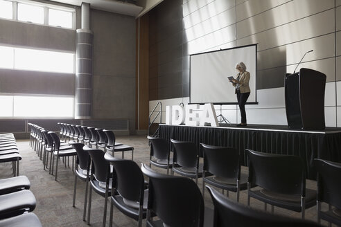 Woman with digital tablet on stage empty auditorium - HEROF27776