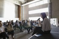 Speaker sitting addressing audience stage near Idea text - HEROF27794