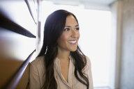 Smiling brunette businesswoman looking away - HEROF27800