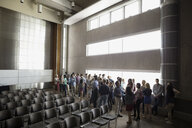 Students socializing along windows in auditorium - HEROF27806