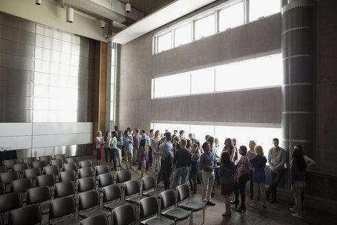 Students socializing along windows in auditorium - HEROF27806