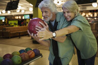 Wife guiding husband bowling at bowling alley - HEROF27824