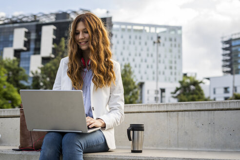 Young businesswoman sitting on stairs in the city, working with laptop - GIOF05778