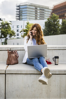 Young businesswoman sitting on stairs in the city, working with laptop and smartphone - GIOF05781