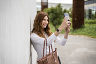 Young businesswoman commuting in the city, taking selfies - GIOF05805