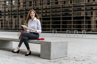 Young businesswoman sitting on bench in the city, using digital tablet - GIOF05814