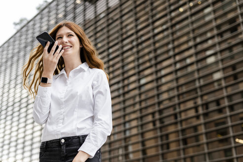 Young businesswoman in the city, using smartphone - GIOF05820