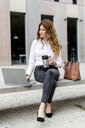 Young businesswoman sitting on bench in the city, working with laptop, drinking coffee - GIOF05826