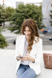 Young businesswoman commuting in the city, using smartphone - GIOF05844