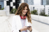Young businesswoman commuting in the city, using smartphone - GIOF05847