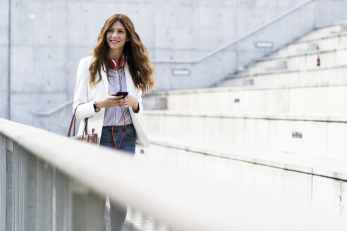 Young businesswoman commuting in the city, using smartphone - GIOF05856