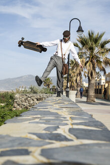 Man with longboard balancing on a wall - KBF00588