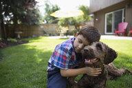 Affectionate boy hugging dog on lawn - HEROF27835