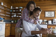 Affectionate young couple texting in cabin kitchen - HEROF27838