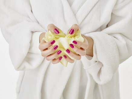 Young woman, hands with varnished nails and rose petals - RORF01760