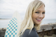 Portrait smiling blonde female surfer with surfboard - HEROF27842