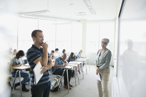 Professor and classmates watching college student at whiteboard - HEROF27863