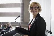Portrait confident professor at podium in auditorium - HEROF27884