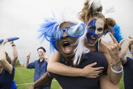 Portrait enthusiastic fans in blue piggybacking and celebrating - HEROF27887
