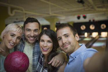 Portrait smiling friends hugging at bowling alley - HEROF27893
