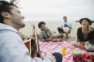 Friends hanging out playing guitar picnicking on beach - HEROF27917