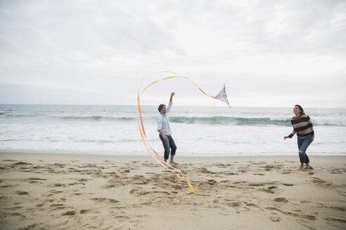 Couple flying a kite on beach - HEROF27920
