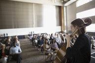 Female cellist performing for audience in auditorium - HEROF27938